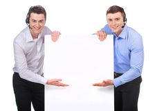 Smiling customer service male operator pointing to blank white billboard. Royalty Free Stock Photo