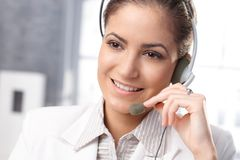 Smiling customer service representative. Closeup portrait of smiling customer service representative using headset, hand on microphone royalty free stock photo