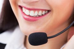 Smiling customer service representative. Closeup of smiling female customer service representative with microphone Stock Images
