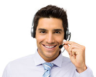 Smiling Customer Service Representative Talking On Headset. Portrait of smiling customer service representative talking on headset against white background Stock Photos