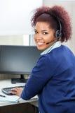 Smiling Customer Service Representative Using. Side view portrait of smiling customer service representative using computer at desk in office stock images