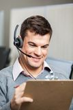 Smiling Customer Service Representative Wearing. Headset while holding clipboard in office Stock Photography