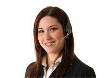 Smiling customer service woman. Attractive young woman with brown hair and red highlights and telephone headset smiles at the camera; isolated on white Royalty Free Stock Images