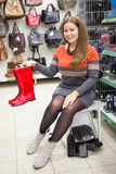 Smiling customer showing red rainboots when dressing shoes Royalty Free Stock Image