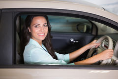 Smiling customer sitting at the wheel of a car for sale Royalty Free Stock Photography