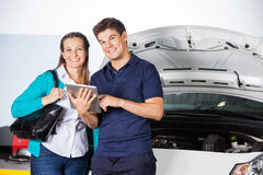 Smiling Customer Standing With Mechanic Holding Digital Tablet. Portrait of smiling female customer standing with mechanic holding digital tablet in garage Stock Photos