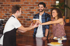 Smiling customers getting take-away cups Royalty Free Stock Image