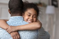 Smiling cute african american child daughter hugging dad feeling love. Smiling cute african american daughter hugging dad feeling love, happy small mixed race royalty free stock photography
