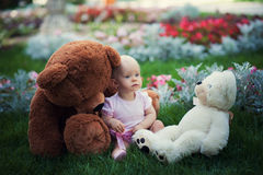 Smiling cute baby-girl on green grass with teddy bears toys Stock Photography