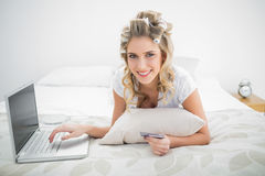 Smiling cute blonde shopping online using laptop Royalty Free Stock Images