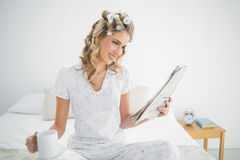 Smiling cute blonde wearing hair curlers reading newspaper Stock Images