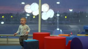 Smiling cute boy playing with big cubes in a children`s play area at the airport. Action at night in slow motion stock footage