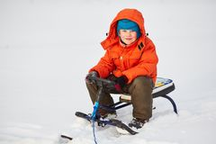 Smiling cute boy sitting on his snow scooter. Child walking on snow outdoors Royalty Free Stock Image