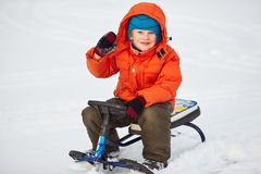 Smiling cute boy sitting on his snow scooter. Child walking on snow outdoors Royalty Free Stock Photos