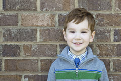 Smiling cute boy up against a brick wall. Smiling cute boy standing up against a brick wall Royalty Free Stock Images
