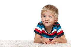 Smiling cute boy on the white carpet Stock Photo