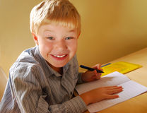Smiling cute boy writing stock photo