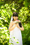 Smiling cute bride smelling bouquet at park Royalty Free Stock Photography