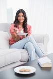 Smiling cute brunette sitting on couch holding hard boiled egg Stock Image