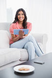 Smiling cute brunette sitting on couch holding tablet Stock Photography