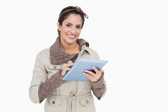 Smiling cute brunette in winter fashion holding tablet Royalty Free Stock Photos