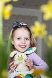 Smiling cute child with easter eggs and plush bunny. Easter Stock Photography