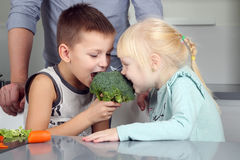 Smiling cute daughter and son biting a  broccoli. Little children  playing with vegatable with father. Royalty Free Stock Image