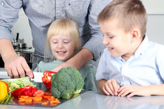 Smiling cute daughter and son cooking a dinner. Little children chopping a colorful pepper with father. Smiling cute daughter and son cooking a dinner. Little stock images