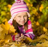 Smiling cute girl against the leaves Stock Photos