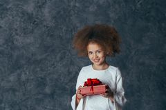 Smiling cute girl with curly hair holding a gift with a red bow royalty free stock photos