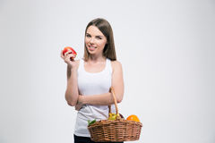 Smiling cute girl holding basket with fruits. Portrait of a smiling cute girl holding basket with fruits isolated on a white background Royalty Free Stock Images