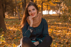 Smiling cute girl in Scharfe sits in autumn Park Royalty Free Stock Photos