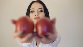 Smiling cute girl showing a juicy dark red apples to camera 4K stock video footage