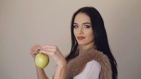 Smiling cute girl showing a juicy green apples to camera 4K stock video footage