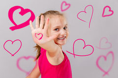 Smiling cute girl showing pink hearts on valentines day. Stock Photography