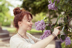 Smiling Cute Girl Smelling Pretty Purple Flowers Stock Image