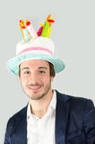 Smiling, cute guy with funny birthday cake hat Royalty Free Stock Photos