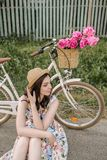 Smiling cute happy girl in dress and hat is seatng near her retro bicycle with flowers in the buncket. Green sunny park. Smiling cute happy girl in dress and hat Royalty Free Stock Image