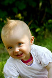 Smiling Cute infant in nature. Beautiful smiling infant on a meadow Stock Image