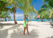 Smiling cute litlle girl standing on tropical Cuban beach and holding fluffy palm leaf Royalty Free Stock Photos