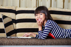 Smiling cute little asian girl with a laptop Royalty Free Stock Photo