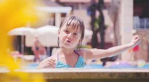 Smiling cute little child girl in pool in sunny day stock images