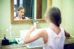 Smiling cute little girl brushing teeth in bathroom. Hygiene con stock photography