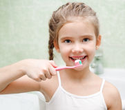 Smiling cute little girl brushing teeth stock images