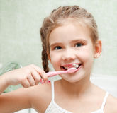 Smiling cute little girl brushing teeth royalty free stock photo