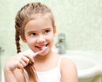 Smiling cute little girl brushing teeth stock photography