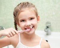 Smiling cute little girl brushing teeth in bathroom royalty free stock photos