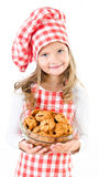 Smiling cute little girl in chef hat holding bowl with cookies Stock Photo