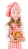 Smiling cute little girl in chef hat holding bowl with cookies. Isolated on a white Royalty Free Stock Photography