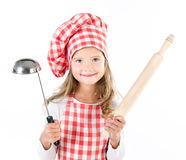 Smiling cute little girl in chef hat with ladle and  rolling pin. Isolated on a white Royalty Free Stock Photo